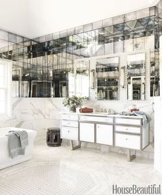 In a Tenafly, New Jersey, bathroom, the Art Deco allure of mirror and marble gets a cool, sleek update from designer Nancy Epstein. Charleston antiqued mirror adds a touch of mystery to a room wrapped in Calacatta Gold marble and with inserts of Arpell Bianco mosaic tile, all by Artistic Tile. Medicine cabinets by Robern accented. Sconces by Visual Comfort. Marcelle faucet by Waterdecor. Restoration Hardware towels.