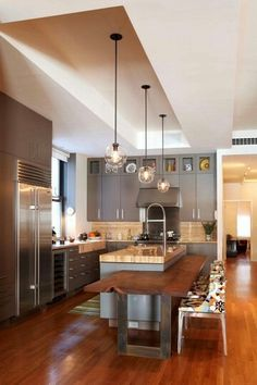 This kitchen has a industrial feel to it with the combination of wood and steel. The pendant lighting helps soften up the island  along with  adding the lower wooden tier level  for serving.