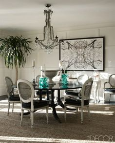 High ceiling - molding - round table - chairs - chandelier + aqua glass candlesticks - art