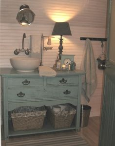 dresser as sink vanity....I love the way they put the sink to the side and dressed the vanity with a lamp.  Feels like a cozy bedroom.  Love this!