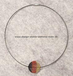 Halsreif aus nylon-ummanteltem Edelstahl mit Drehverschluss (ca. 46 cm lang) wahlweise in schwarz, rot oder gold (bitte bei Bestellung angeben) mit einer dreifarbig gestrickten DEUTSCHLAND KUGEL,...
