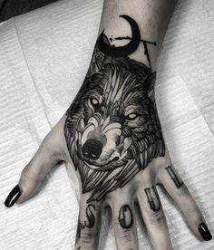 tatuajes de lobos pequeños en la mano de una mujer