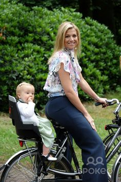 Princess Maxima and Princess Ariane of the Netherlands ride a bike during a Dutch Royal Family photocall at Landgoed de Horsten