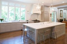 A pair of white lanterns stands over a gray kitchen island with legs topped with white marble lined with clear acrylic counter stools, CB2 Vapor Counter Stools.