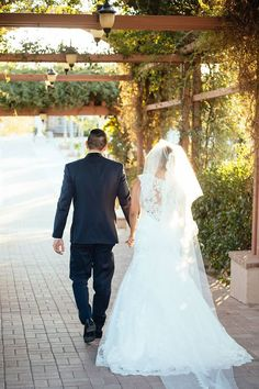 The bride and groom under a vine covered archway during their winery wedding at Mount Palomar Winery in Temecula. A stunning cathedral length veil and a lace backed dress during their Fall winery wedding in Temecula. #mountpalomarwinery