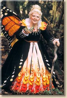Butterfly Monarch The butterfly Queen with her monarch wings and monarch-inspired black velvet gown, strolls through the garden with a young monarch caterpillar.  - by Martha and Marianne