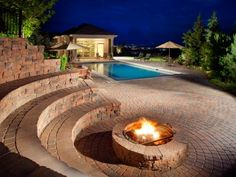 Integrate+your+pool+with+a+well-designed+patio.+An+attached+fire+pit+with+built-in+curved+seating+and+a+dining+area+make+this+pool+patio+area+family+friendly+and+ideal+for+entertaining.+Photo+courtesy+of+Belgard+Hardscape