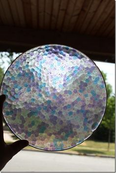 How to make a sun catcher out of pony beads found at any craft store. Place the beads in a metal pie pan. The tighter the beads, the thicker the sun catcher. Bake @ 400 degrees for about 20 minutes . No need to grease pan...it will pop out by itself when it cools.  Drill a hole and run a cord through to hang or use suction cup to place on window. Nice gift!