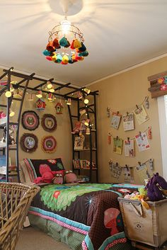 Vintage laundry cart used for toy storage; Bed canopy made from garden trellis with wood shelves added; Ceiling fixture created from a vintage garden basket and tassel key chains; Window valance made from salvaged wood scraps; jump rope and clothes pins used to hang artwork