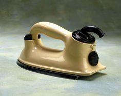 HMV 'Ceramic' electric iron, c 1936.  This HMV heat control iron has a powerful heating element and the construction and design allows minimal heat loss from the body. The body and integral handle are made of glazed porcelain (chrome and painted versions were also available) and the sole plate is heavily chromium plated to conduct heat well and glide smoothly.