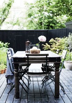 Outdoor dining space with  black table and chairs and single flower as centerpiece.