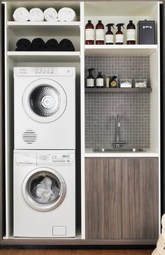 Stacked washer and dryer with utility sink all in one closet with shelves for organizing laundry supplies.