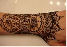 """Henna tattoo design. I tried this one on the palm side of a friend's hand and forearm, and added a semicircle radiating stripes and little petals on the wrist flower, expanding the design to the edge of the palm. The detailing was easy (mostly curlicues and """"fish scale""""), but it was time consuming (~1 hr)."""