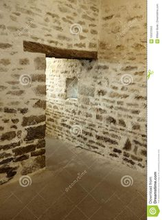 Photo about An elegant old doorway inside a barn in France with stone walls a small window and a door framed with an old wooden header. Image of french, france, door - 105372553