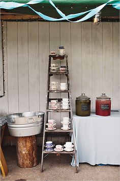 """Drink station idea with mojitos and pink bubbly punch and TEACUPS! The bride """"thrifted"""" them (lucky). We can't do this, but it's such a quirky idea: teacups instead of mason jars. Very Alice in Wonderland!"""