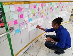 Hundreds of messages of hope and support for refugees are posted all over a wall.