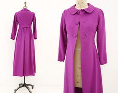 Stunning 1960s vintage maxi coat in a beautiful magenta / purple, mod empire cut features very fitted high waist with A line sweep to floor, Peter Pan collar, lovely gathered full back with box pleat and military-style buttoned belt. Big covered bodice buttons, narrow fitted sleeve - completely wonderful and unique.  fits like: Extra Small  bust: 33 waist: 28 @ natural waist hip: 39 length: 49.5 sleeve: 22 shoulder: 14  condition: excellent, pristine aside from a small dark mark at lower...