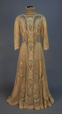 Tea Gown: 1900's, high neck cotton bastiste elaborately decorated with tucks, embroideries and various laces.