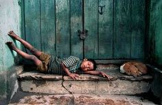 """Hard World, 2007.-Hard World, 2007. Sudipto Das said: """"It portrays the socio-economic condition of third world countries – lack of housing, inappropriate hygiene, and unhealthy environments increase the risk of exposure to diseases and street violence for poor children such as the boy in the picture.""""  Photograph: Sudipto Das/Ciwem Environmental Photographer of the Year"""