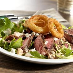 Ribeye steaks marinated in a sassy dressing are grilled and sliced to top a savory green salad with crumbled goat cheese and crunchy onion rings.
