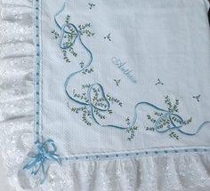 Manta bordada feita em pique, forrada, bordada apenas em um lado. As cores variam de acordo com o estoque ou escolha do Cliente.