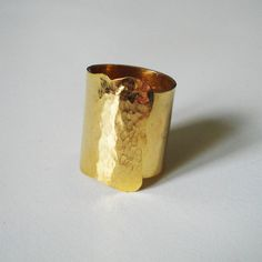 This is an one of a kind ring made from a bronze sheet then soldered and hammered and finally gold plated 24K.
