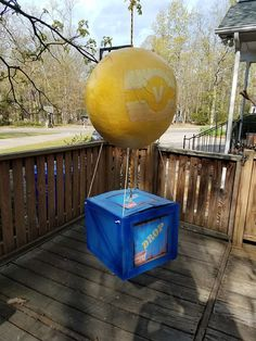 Fornite supply drop pinata. Balloon is made out of paper mache applied to a large balloon. Spray painted yellow and V logo printed and glued on. Box made out of lightweight cardboard box with additional strips of cardboard glued on for edging. Spray painted in two shades of blue. Drop box images printed and glued on four sides. One thick rope connects from the box through the top of the balloon to hang from. Four smaller ropes connect the balloon to the box.