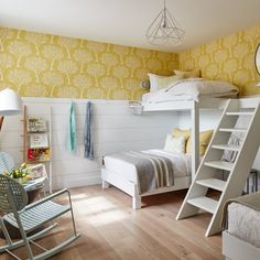 Basement bedrooms has its challenges - it can be dark and gloomy. Sticking to a palette like this sunny yellow wallpaper and white paint can make a big difference.  For more basement bedroom inspiration: