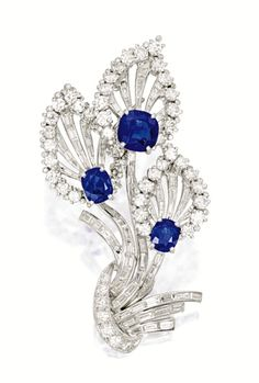 SAPPHIRE AND DIAMOND BROOCH, TIFFANY & CO.   Of foliage design, set with three cushion-shaped sapphires together weighing approximately 7.12 carats, to a background set with brilliant-cut and baguette diamonds together weighing approximately 7.00 carats, mounted in platinum, signed.