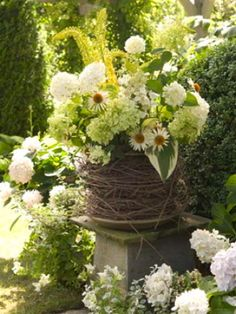 Stack grapevine wreaths over planter.