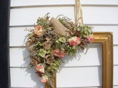 Antique gold Victorain frame with burlap bow, burlap roses, dried roses, and other dried flowers