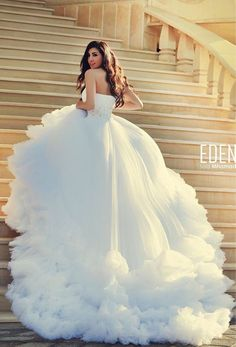 White one shoulder runched wedding dress, running within its cloud of soft ruffled petticoats and over skirting. The dress beckons for touch and attention. Said Mhamad Photography.