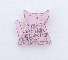 A handmade folkgarden cat pin with a Bill Watterson quote.