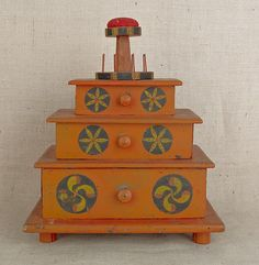 """Realized Price: 2015.00    Pennsylvania painted pine table top sewing stand, late 19th c., with pinwheel and philphlot decoration on an orange ground, 18"""" h., 15"""" w."""