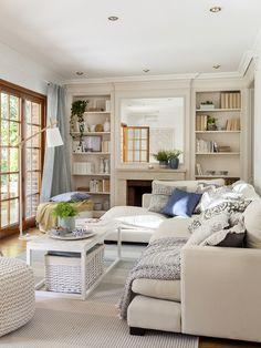 Pequeño salón en tonos claros con sofá en forma de L y dos estanterías con libros a cada lado de la chimenea_00443158 O