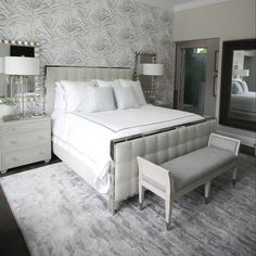 This view of the master shows off statement wallpaper by @wallquestofficial and the clean lines of the gorgeous furnishings! Such a comfy and beautiful bedroom.  bed: @bernhardtfurniture linens: @matouklinens  rug: @stantoncarpet bench: @bernhardtfurniture lamps and mirror: @uttermostcompany lounge chairs: @bernhardtfurniture wallpaper: @wallquestofficial pillows: @schumacher1889  photo: @palmbeachcreative