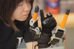 The Supernumery Robot Fingers, or SR, is a device that adds robo-digits on your hand. It has a special sensor that reacts to normal movements of your hand. The extra fingers are large on purpose to provide an extended reach and to hold big objects with firm grip.