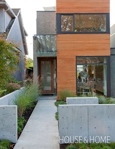 Designed by David Nicolay of Evoke International Design, this home has big presence thanks to the bold façade, large windows and modern landscaping. The wooden siding contrasts with the concrete half walls, and graphic grasses add visual interest. | Photographer: Janis Nicolay | Designer: Nancy Riesco