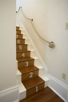 Cute way to add a nautical touch to bare stairs.  And LOVE the rope railing.