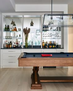 A Basement Wet Bar Boasts White Cabinets Paired With Black Quartz Countertops Fitted Square Sink And Brushed Nickel Faucet Against Mirrored