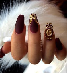 Matte nails are a selection of this lady also. King's dark red color is always in fashion, and with gold rhinestones looks very luxurious.