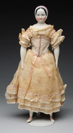 "1850's era glazed china shoulder head with molded and pate facial features with long black curls touching the shoulder in back, covered by a white smooth bonnet with ridged front and tied under the chin. The body is possibly a mid 20th century replacement and is stuffed muslin with china arms and legs with molded and painted shoes. She has been redressed in all antique fabric and outer corset is cinching the waist. Condition (Very Good). Size 12"" T."