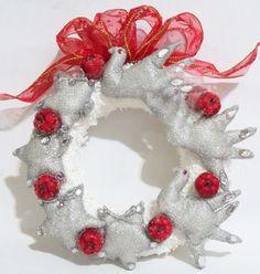 """Guirlanda com base de isopor coberto com fita de cetim branco e aplicação de """"flocos de neve"""", ornamentado com estrelas e pássaros de tecido metalizado e pequenas frutas vermelhas."""