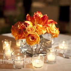low centerpieces: clear glass vases displayed a variety of fall-colored flowers like orange and yellow roses and mango calla lilies.