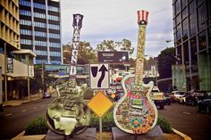 """They've been a familiar site to anyone travelling along the Sunset Strip over the last year– and now a collection of gigantic guitar sculptures will sell for charity on February 21, 2104.   Bonhams hosts the """"GuitarTown"""" sale, which offers twenty four 10ft-tall Gibson guitars inspired by the rich music history of the Strip."""