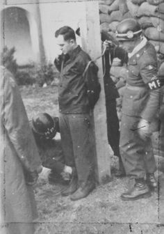American military police tie Peter Chemy to a post prior to his execution by firing squad. A Polish national liberated from a concentration camp in May 1945, he spent the first few months of his freedom adrift in Germany. On a  winter night of that year, he found refuge in the home of a German family: husband, wife, and daughter. After they had gone to sleep, Chemy found a hatchet and murdered them in their beds. He was tried by an American tribunal and executed by firing squad.