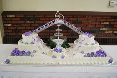 "Wedding - Base of cake is 51"" x 19"" - 4 sheet cakes, with a 6"" single layer in the front, and two 8"", 12"" round tiers on the side.  Working fountain and bridge/stair set."