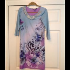 Multi-color Embellished Dress This beautiful turquoise and purple dress is accented with a floral and animal print pattern. Beaded embellishments are sewn near the scoop neckline. Argenti Dresses Midi