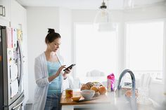 Woman in pajamas texting in breakfast kitchen