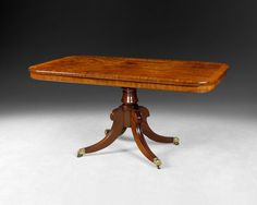A particularly good Regency Period Mahogany breakfast table, the rectangular, fiddle- back and flame figured and crossbanded tilting top above a column raised on moulded sabred legs terminating in brass feet and casters. C.1820